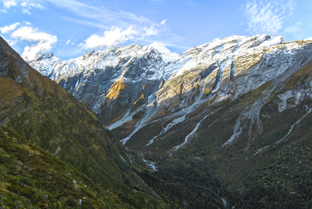 Mt. Aspiring is seen in the distance from a steep trail leading to Liverpool Hut in the Matukituki Valley on New Zealands south island. Stock Photo