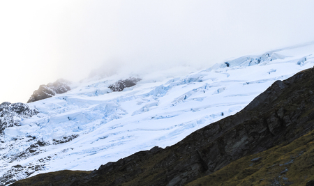 Fog rolls in over a crevassed glacier in the Mt. Aspiring National Park on New Zealands south island.