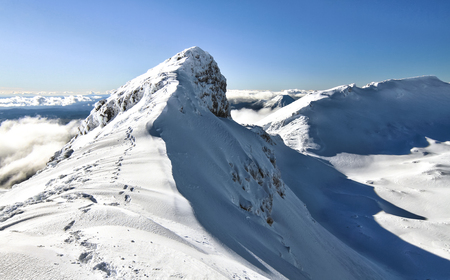 Footsteps lead along the narrow summit ridge of Mt. Ruapehu in New Zealand.