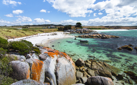 Bright orange lichen covers the rocks and gives the Bay of Fires its name. Tasmania, Australia.