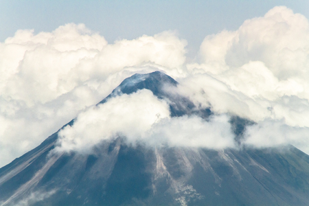 The summit of Volcan Arenal among the clouds in central Costa Rica.