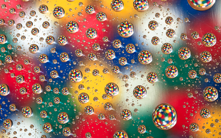 Droplets of water stuck to a thin pane of glass reflect a group of colors behind it, giving the impression that spheres of color are floating in space.