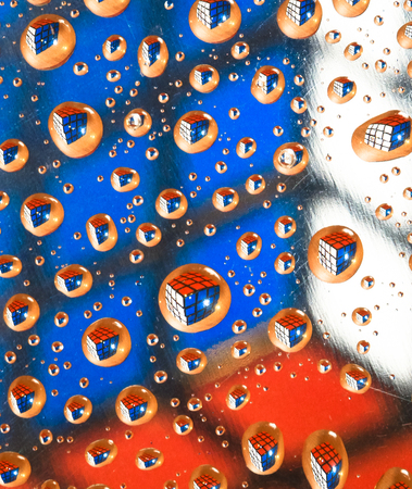 A cube puzzle is reflected in water droplets, giving the appearance that they are floating in space.