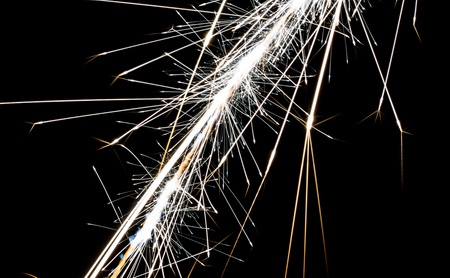 Large sparks from a magnesium fire starter explode in the air.