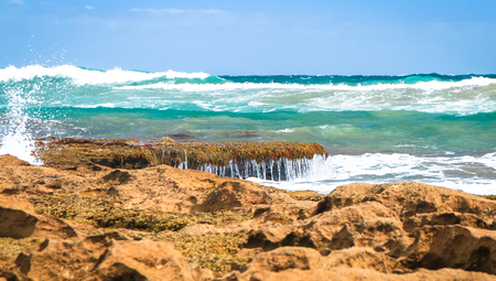 Green waves crashing on a rocky shore in a rough and rugged section of Australia's coastline. Barwon Heads, Victoria. Stock Photo