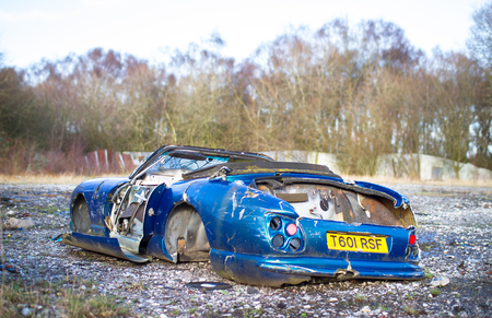 An old wrecked sports car sits on the ground at the abandoned Furber's Scrapyard in Shropshire, England.
