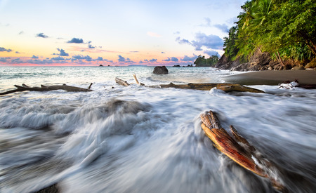 Long exposure of waves crashing against driftwood at sunset on the west coast of the Osa Peninsula, Costa Rica.
