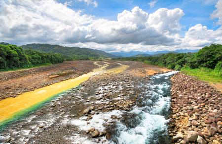 A clean stream converges with the Rio Sucio near Guapiles, Costa Rica.