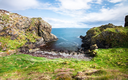 A small inlet in a rocky coastline provides access to a small rocky beach on the island of Islay, Scotland, UK.