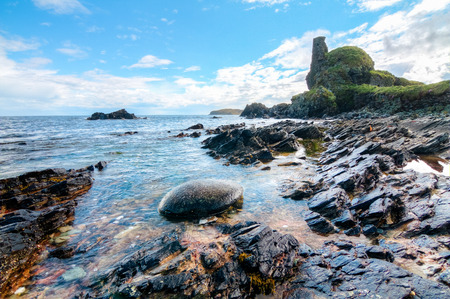 Jagged rock layers and boulders smoothed by the ocean are seen at an intertidal zone on the island of Islay, Scotland, UK.