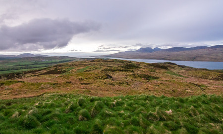 View of upland fields, barren landscapes, the ocean, and hills on the island of Jura, as seen from the Island of Islay, Scotland.
