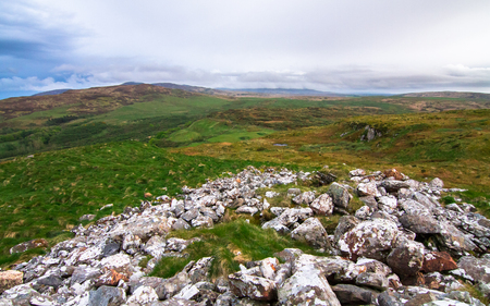 Looking south from the rocky Am Tamhanachd peak towards upland grazing fields on the island of Islay, Scotland. Stock Photo