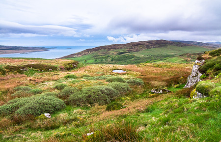Looking south from Am Tamhanachd peak towards upland grazing fields and the ocean on the island of Islay, Scotland.