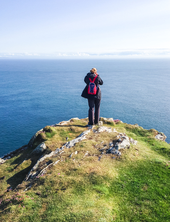 A hiker with a small red backpack stands on the edge of a cliff overlooking the ocean on a sunny day. Photographed on the tip of the Oa Peninsula on the island of Islay in Scotland. Stock fotó