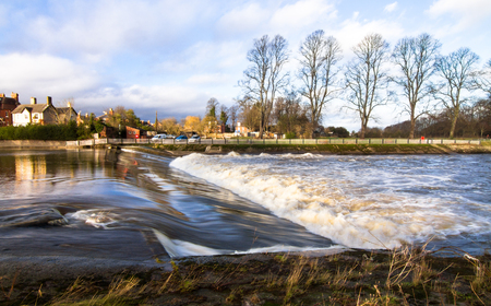 Water flows over a manmade weir on the River Severn in Shrewsbury, Shropshire, England.
