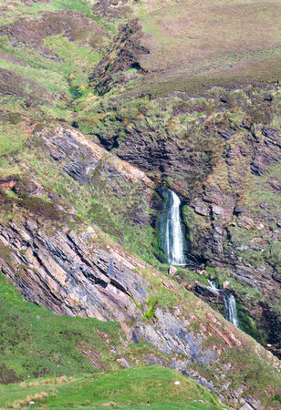 A waterfall tumbles through a narrow rocky gully among grassland in the Oa Nature Reserve on the island of Islay in Scotland.