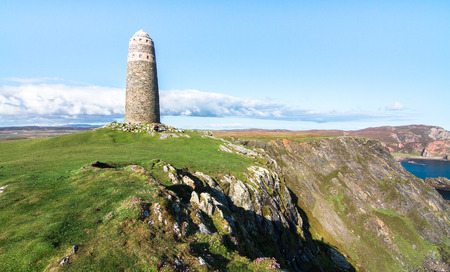 A large rock tower sits on a grassy field at the tip of the Oa Peninsula on the island of Islay in Scotland.