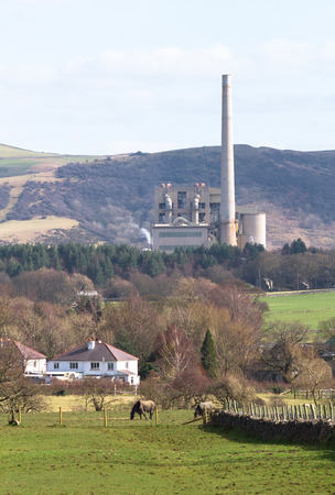 A large factory with a very tall smoke tower sits among agricultural fields in the Peak District, England. 写真素材 - 120579856