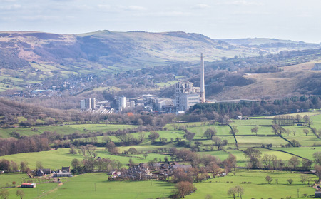 A large factory with a very tall smoke tower sits among agricultural fields in the Peak District, England.