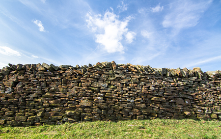 Stone wall next to a grassy agricultural field on a sunny day in the Peak District, England.