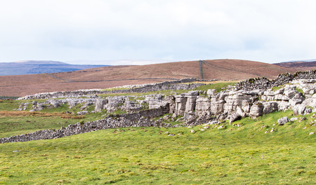 Natural rock cliffs sit next to manmade rock walls in a grassy and barren landscape in the Peak District, England. 免版税图像