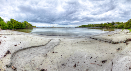 Streams of water flow into a small bay in this HDR image taken on the island of Islay in Scotland. Archivio Fotografico - 120581639