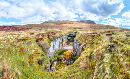 A large rock chasm with massive cliffs in a barren grassy landscape is seen below the peak of Pen-y-Ghent in the Peak District, England.