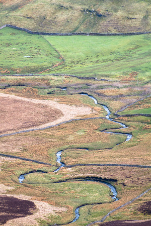 A small stream meanders through farmland in the Peak District, England. Stock Photo
