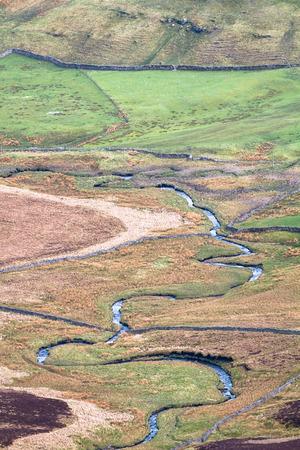 A small stream meanders through farmland in the Peak District, England. 免版税图像