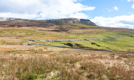 Pen-y-Ghent towers above the barren landscape and a public walking trail in the Peak District, England.