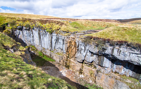 A large rock chasm with massive cliffs in a barren grassy landscape near the peak of Pen-y-Ghent in the Peak District, England. Stock Photo