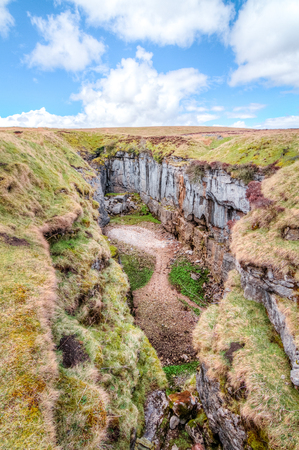 A large rock chasm with massive cliffs in a barren grassy landscape near peak of Pen-y-Ghent in the Peak District, England.