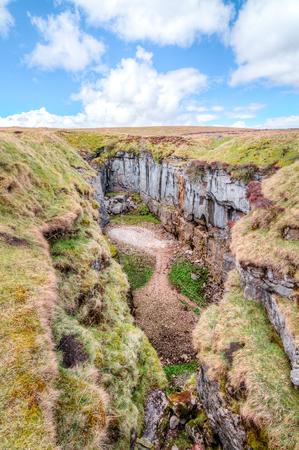 Un grand gouffre rocheux avec des falaises massives dans un paysage herbeux stérile près du pic de Pen-y-Ghent dans le Peak District, en Angleterre. Banque d'images