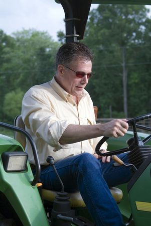 befuddled: Man seemingly confused as to how to operate the tractor he is sitting on. Stock Photo