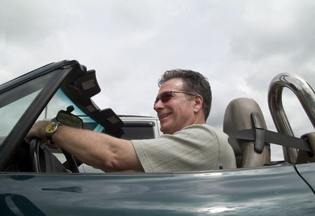 A man enjoying driving his convertible sports car with the top down. Stock Photo