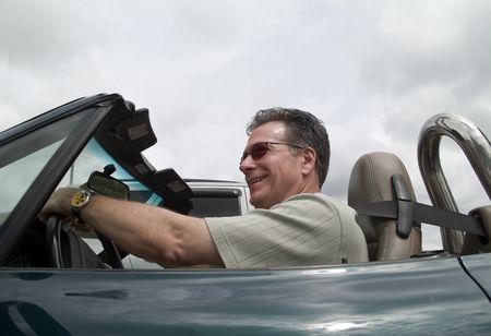 cabrio: Een man die onder het rijden zijn converteerbare sportieve auto met de top-down.