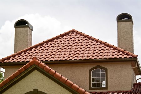 The terracotta roof of a building with two chimmeys.