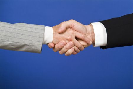 substantiate: A picture isolated on blue of a businesman and a business woman engaged in a handshake.