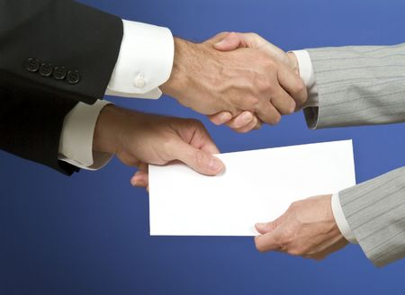 Two people shaking hands and exchanging a white envelope with available copy space for adding text.