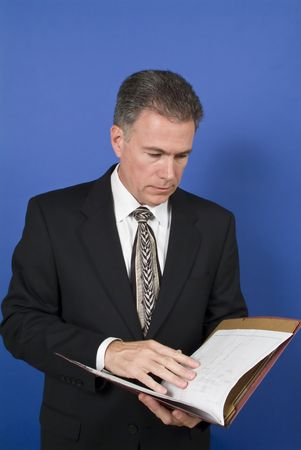 assess: A businessman, standing in front of a blue background, reviewing or conducting a briefing on the contents of the folder.