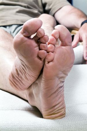 A picture of a mans feet whose tonails are in need of a good pedicure.  photo