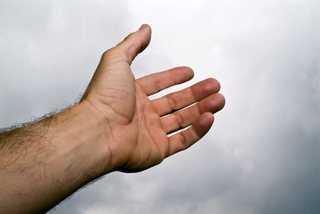 A mans hand reaching towards the sky as if in need of a helping hand.