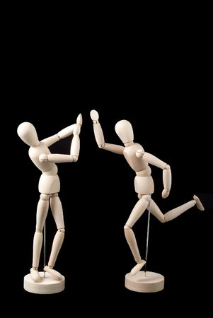 Two little faceless mannequins, one positioned in a posture of agression, the other in a posture of defense. Stock Photo
