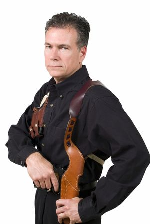grasping: Mature, hansome, white male wearing a shoulder holster with a clip holder drawing from the holster a nine millimeter automatic weapon.