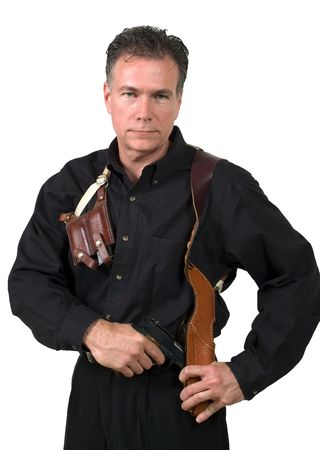 holster: Mature, handsome, white male dressed in black on an isolated background wearing a shoulder holster armed with an automatic pistol.