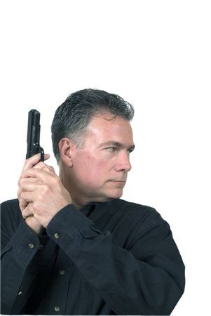 poised: Mature, handsome, white male poised ready for action with a nine millieter automatice weapon grasped firmly in his hands with his finger on the trigger.
