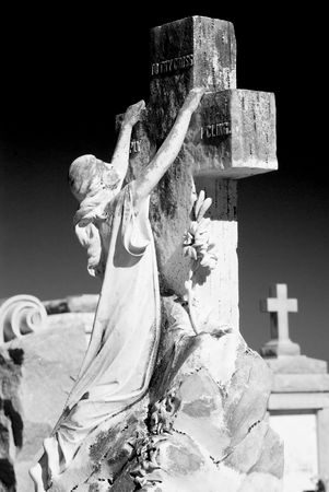 angel cemetery: Cemetery scene with a statue of a woman clinging to a cross in a posture of grief or hope with another cross from another tomb far in the background.