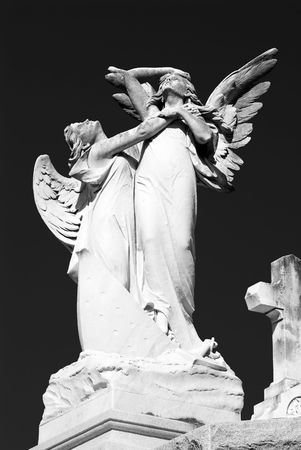 grasping: A statue of two female angels clutching one another in a posture of anguish or despair with a image of a cross in the lower right hand corner of the picture.