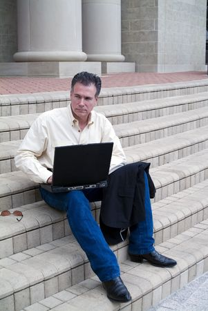 correspond: Man sitting on the steps of a large building with a laptop with an expression of contemplation.