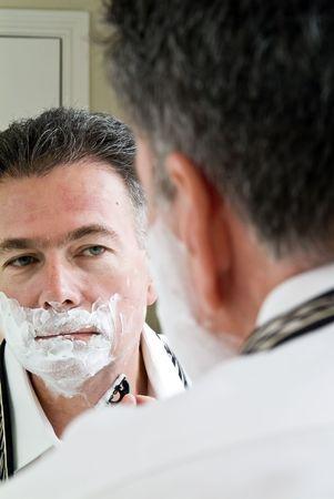 Un hombre mirando en el espejo en el proceso de afeitado.  Foto de archivo - 1228698